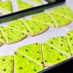 Bright green Christmas tree sugar cookies lined up on a baking tray, with different colored sugar pearls as ornaments.