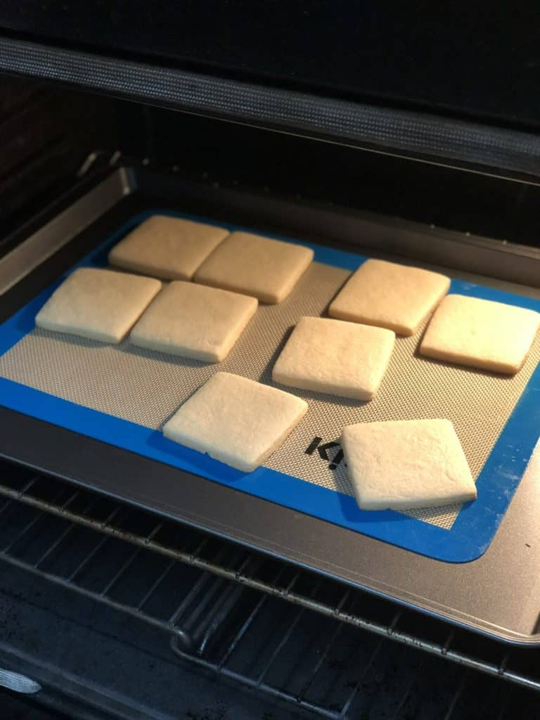 Nine square cookies on a silicone mat lined cookie sheet inside of an oven.