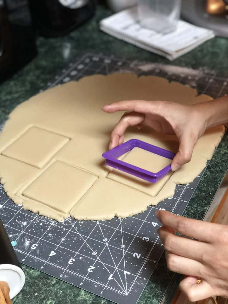 A hand using a purple-colored square-shaped plastic cookie cutter to cut square cookies out of the raw, rolled cookie dough.