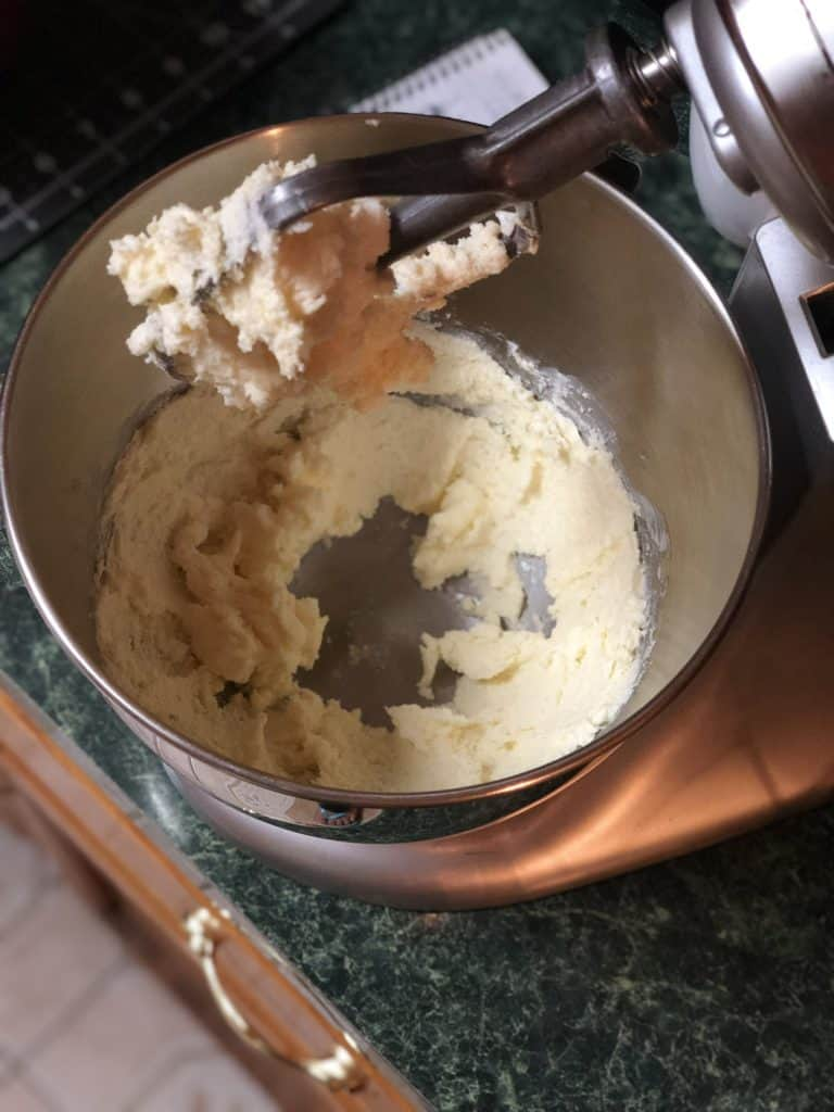 A light-colored creamy mixture of margarine, shortening, and sugar in a silver electric mixer bowl with the paddle attachment raised.