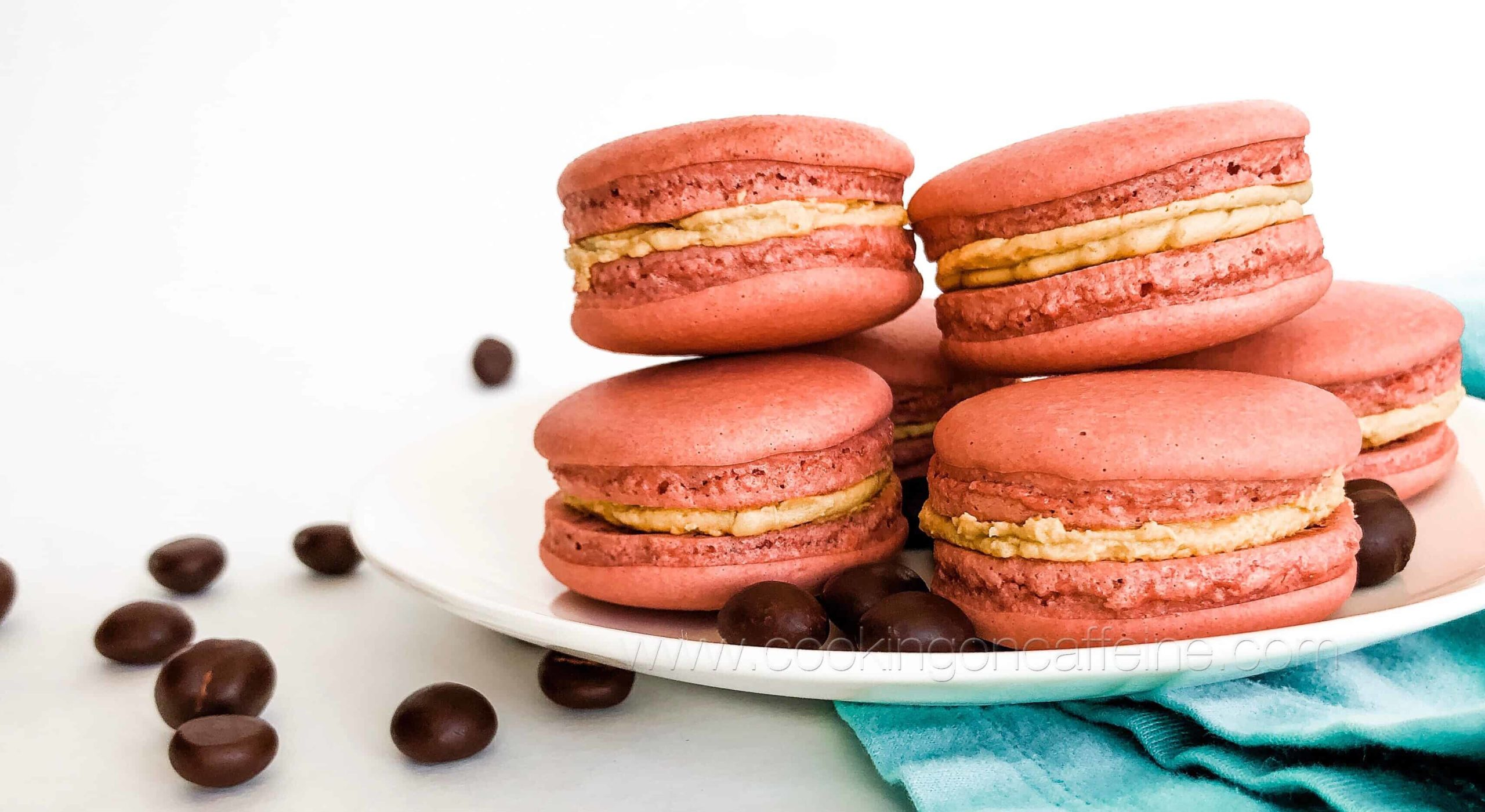 Salmon colored macaron cookies on a white plate, on a sky blue towel and surrounded by chocolate covered coffee beans