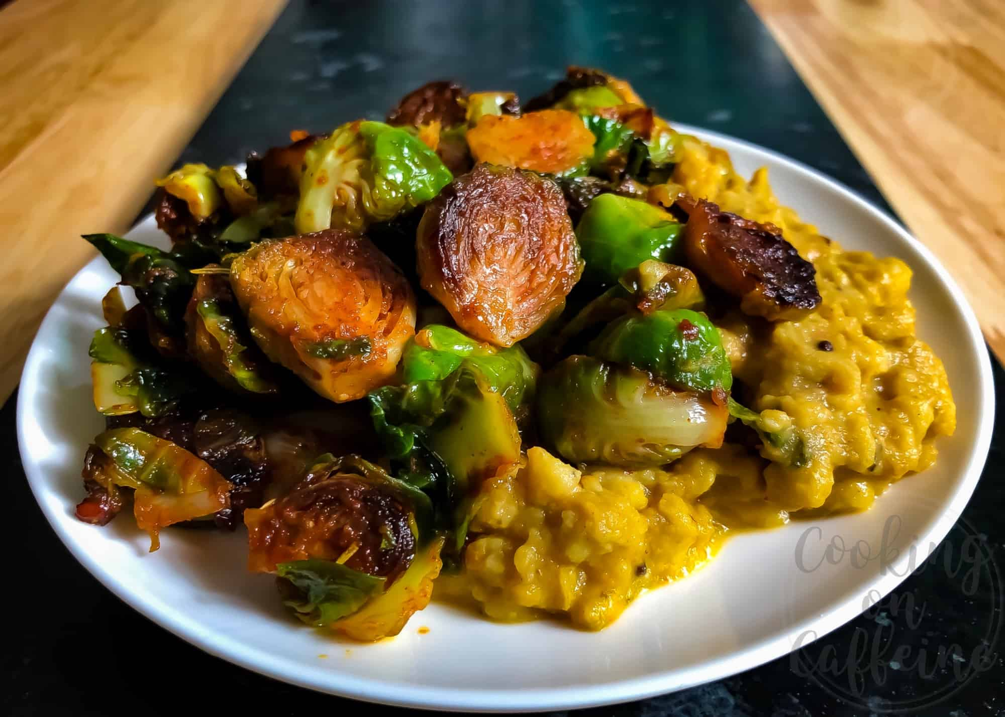 Side shot of seared Brussels sprouts coated in red chili paste and served on top of yellow dahl curry.