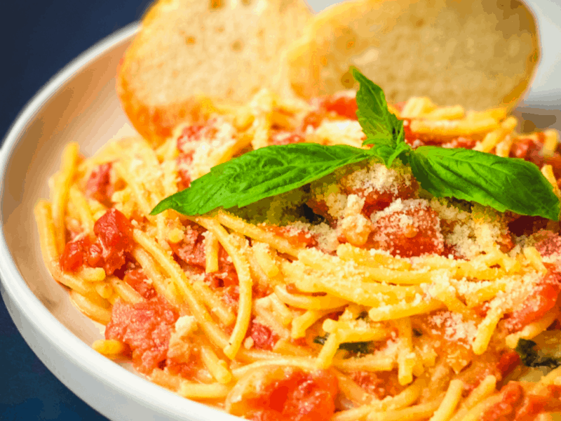 close up of spaghetti and tomato cream sauce, garnished with fresh basil leaves and slices of bread