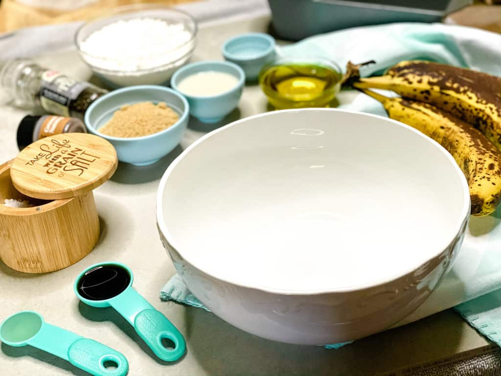 An angled shot of all of the banana bread ingredients with a white mixing bowl in the foreground.