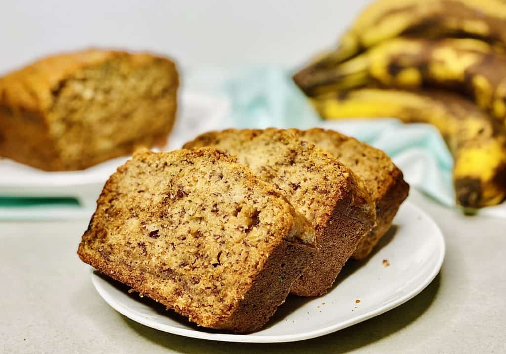 Three slices of banana bread on a white plate, bananas and a cut loaf of bread in the background.