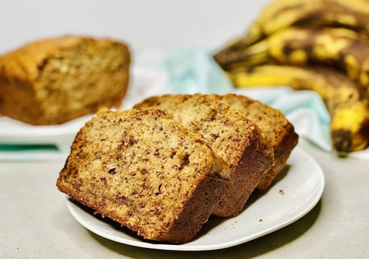 three slices of banana bread on a white plate, with ripe bananas and a sliced loaf in the background