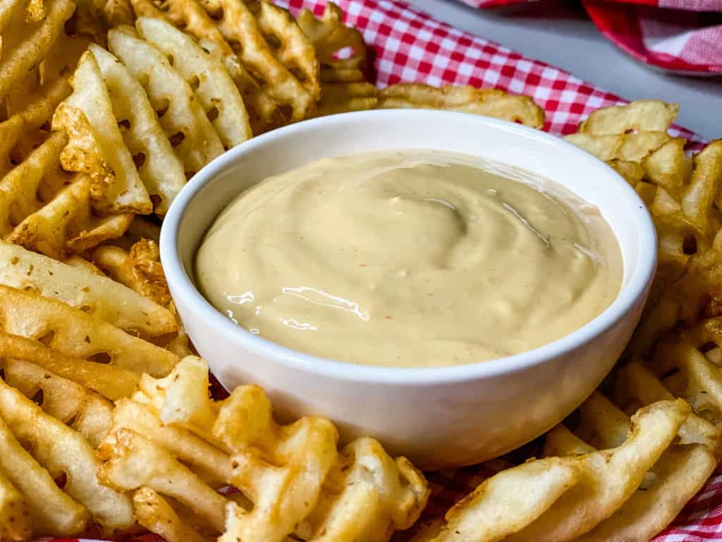 White bowl full of creamy light orange sauce in a bed of waffle fries