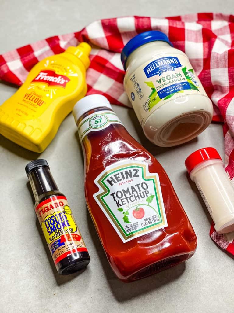 Bottles of vegan mayo, yellow mustard, ketchup, garlic powder, and liquid smoke with a red and white napkin
