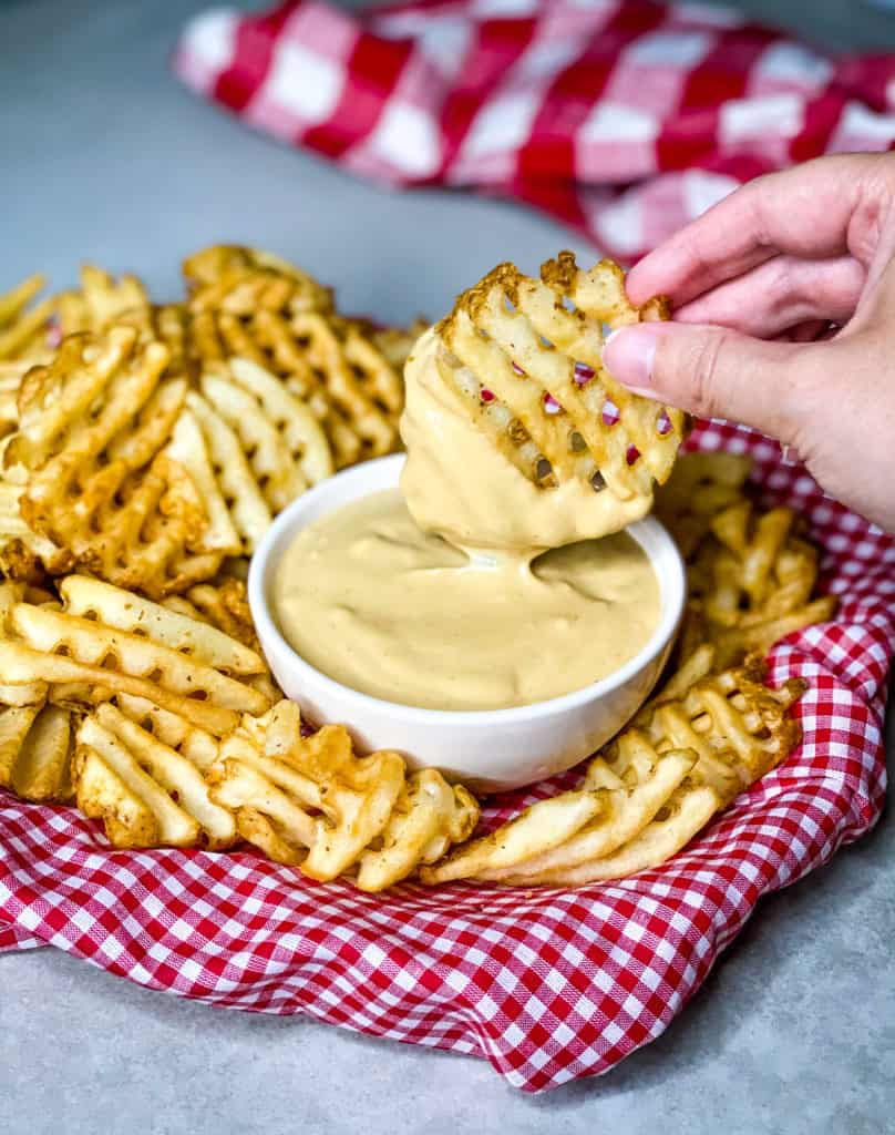 dipping a waffle fry into a creamy light orange sauce