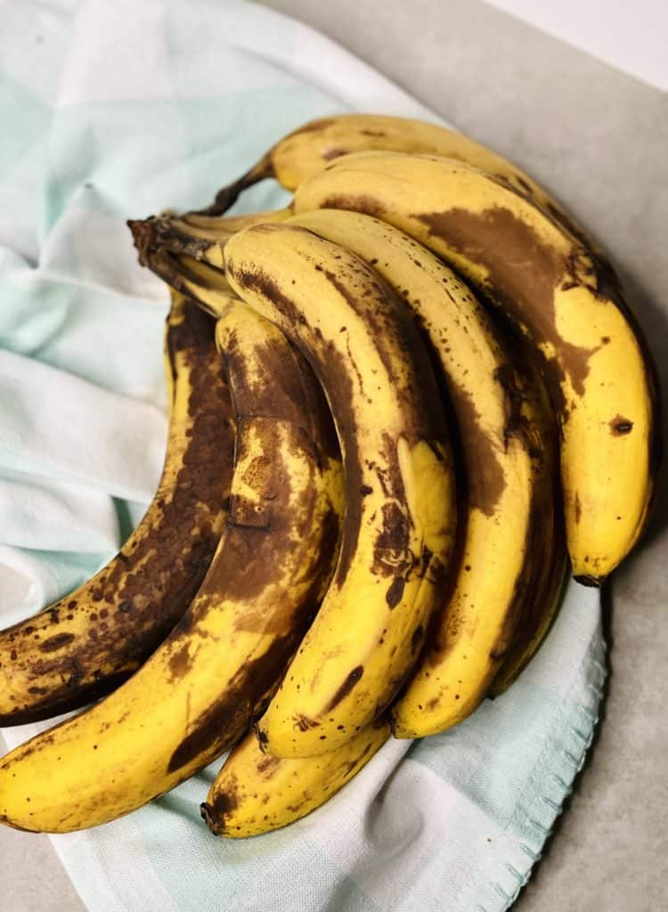 A bunch of really ripe bananas with one super ripe on on the left.