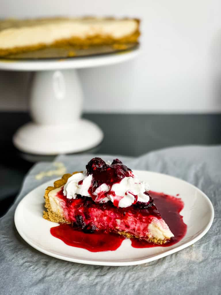 A slice of cheesecake on a graham cracker crust topped with whipped cream and berries, with berry juice running off the sides pooling in the plate.