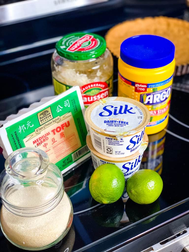A photo showing the ingredients in the cheesecake filling: sugar, medium hard tofu, limes, two small containers of yogurt, a jar of sauerkraut, and corn starch
