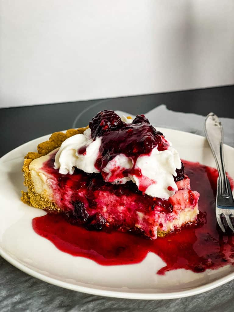 A slice of the cheesecake with berries, whipped cream, lots of berry juice pooling in the plate, a small silver fork and a bite taken from the slice.