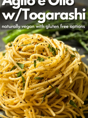 a big mound of delicious spaghetti on a grey plate and broccolini in the background with text on top that reads Oglio e Olio w/Togarashi natrually vegan with gluten free options
